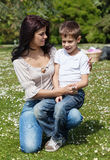 Boy with his mom at picnic. Pretty young women sitting on grass with her son Royalty Free Stock Photography