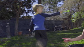 A Boy and his mom play with bubbles in the backyard stock video