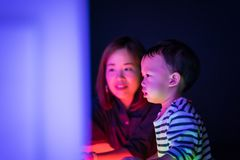 A boy and his mom are playing colorful light cubes. A boy and his mom are playing colorful light cubes together in the dark study room Stock Photos