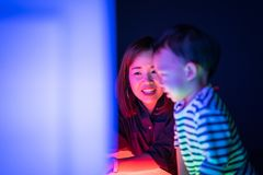 A boy and his mom are playing colorful light cubes. A boy and his mom are playing colorful light cubes together in the dark study room Stock Images