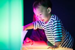 A boy and his mom are playing colorful light cubes. A boy and his mom are playing colorful light cubes together in the dark study room Stock Photography
