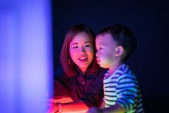 A boy and his mom are playing colorful light cubes. A boy and his mom are playing colorful light cubes together in the dark study room Royalty Free Stock Photo