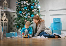 Boy and his mom playing with wooden hammer toy while sitting beside Christmas tree Stock Photo
