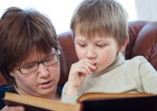 Boy and his mom reading book together Stock Photos