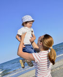 Boy and his mother at beach. Boy is on his mother's hands Stock Image