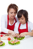 Boy with his mother decorating party sandwiches Royalty Free Stock Image