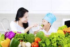 Boy and his mother eat salad. Cute little boy and his mother eating vegetable salad in the kitchen at home Stock Photos
