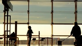 Boy with his mother in the International Airport of Barcelona. Silhouettes of people.  stock footage