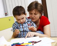 Boy with his mother learns to draw stock image