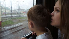 Boy and his mother looking out the window of train. Close-up shot of a little boy with his mother looking out the window of moving train in rainy weather stock video
