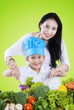 Boy and his mother mixing salad. Portrait of happy little boy and his mother making vegetables salad while smiling at the camera Stock Image