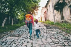 A boy and his mother in the old town. A boy and his mother are walking in the old town. A woman travels with her son in historical places. The child is walking stock photo