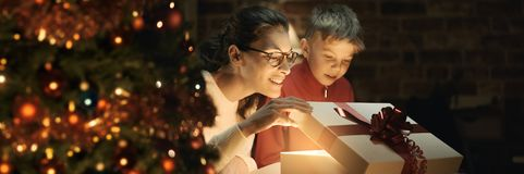 Boy and his mother opening Christmas gifts royalty free stock photos