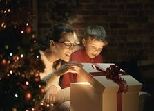 Boy and his mother opening Christmas gifts stock images