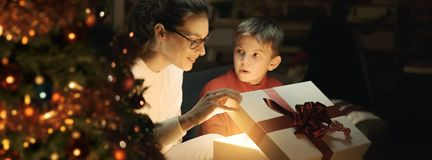 Boy and his mother opening Christmas gifts stock image