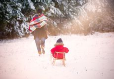 Boy and his mother playing in winter landscape. Child model Royalty Free Stock Images