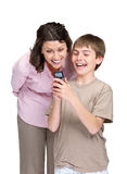 Boy and his mother reading a funny sms on mobile Stock Images