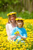 Boy and his Mother Sitting in a Dandelion Field Royalty Free Stock Images