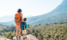The boy and his mother are standing on the top of the mountain royalty free stock photography