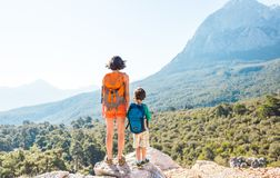 The boy and his mother are standing on the top of the mountain stock photos