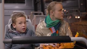 A bus talk. A boy and his mother talk to each other, sitting in a bus, that is going through the night city stock video