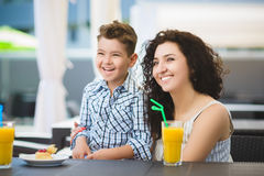 Boy and his mother tasting dessert with juice in resort restaurant outdoor.  Stock Photography
