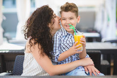 Boy and his mother tasting dessert with juice in resort restaurant outdoor.  Royalty Free Stock Image