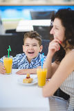 Boy and his mother tasting dessert with juice in resort restaurant outdoor.  Royalty Free Stock Photo