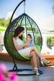 Boy and his mother tasting dessert with juice in resort restaurant outdoor Stock Image