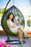 Boy and his mother tasting dessert with juice in resort restaurant outdoor.  Stock Images
