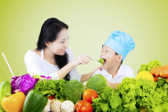Boy and his mother tasting vegetable salad. Cute little boy and his mother tasting vegetable salad, shot with green screen background Stock Photography
