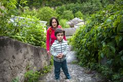 A boy and his mother in the old town. A boy and his mother are walking in the old town. A women travels with her son in historical places. The child is walking stock images