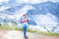 Boy with his newborn baby brother in mountains Stock Photos