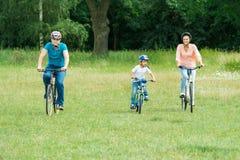 Boy With His Parent Riding Bicycle stock photos