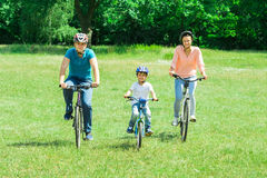 Boy With His Parent Riding Bicycle Royalty Free Stock Photography
