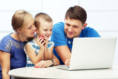 Boy and his parents. Happy family of three at the table with a computer. Boy holds an apple Stock Photography