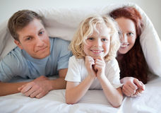 Boy with his parents under bed cover Stock Photography