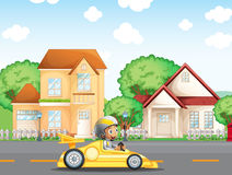 A boy in his racing car across the neighborhood Stock Photography