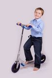 Boy on his scooter Stock Images