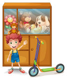 A boy and his scooter in front of his toy collections Royalty Free Stock Photography