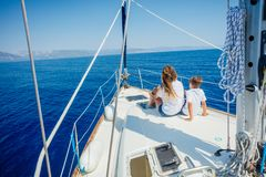 Boy with his sister on board of sailing yacht on summer cruise. Back view of boy with his sister on board of sailing yacht on summer cruise. Travel adventure royalty free stock images