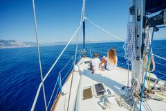 Boy with his sister on board of sailing yacht on summer cruise. Back view of boy with his sister on board of sailing yacht on summer cruise. Travel adventure stock photography