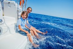 Boy with his sister on board of sailing yacht on summer cruise. Travel adventure, yachting with child on family vacation stock image