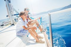 Boy with his sister on board of sailing yacht on summer cruise. Travel adventure, yachting with child on family vacation stock photography