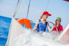 Boy with his sister on board of sailing yacht on summer cruise. Travel adventure, yachting with child on family vacation. Kid clothing in sailor style Royalty Free Stock Images