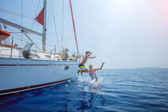 Boy with his sister jump of sailing yacht on summer cruise. Travel adventure, yachting with child stock images