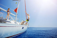 Boy with his sister jump of sailing yacht on summer cruise. Travel adventure, yachting with child Stock Photos