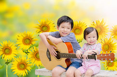 Boy and his sister play guitar and sing Stock Photo