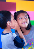 Boy and His Sister. The boy say something to his sister's ear Stock Image