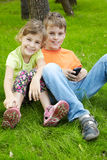 Boy and his sister sit on grass under tree Stock Photos